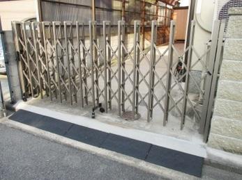 車庫の伸縮門扉が古くなり、取り換えをお考えの方に向けた施工事例です。<br>伸縮門扉は接続部分のリベットと、コマが大抵ボロボロになります。<br>そこに気を配った商品を選んでください。<br>防犯性能も上がっております。<br>■三協アルミ 伸縮門扉 エクモアLH の施工事例です。